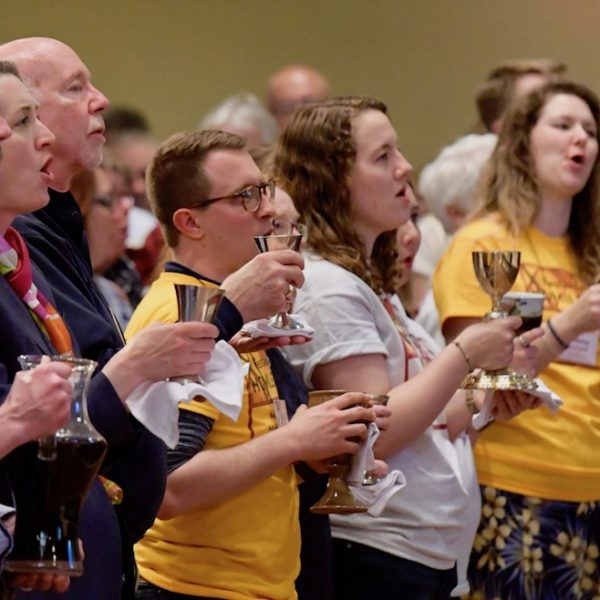 worship participants holding communion chalices and singing