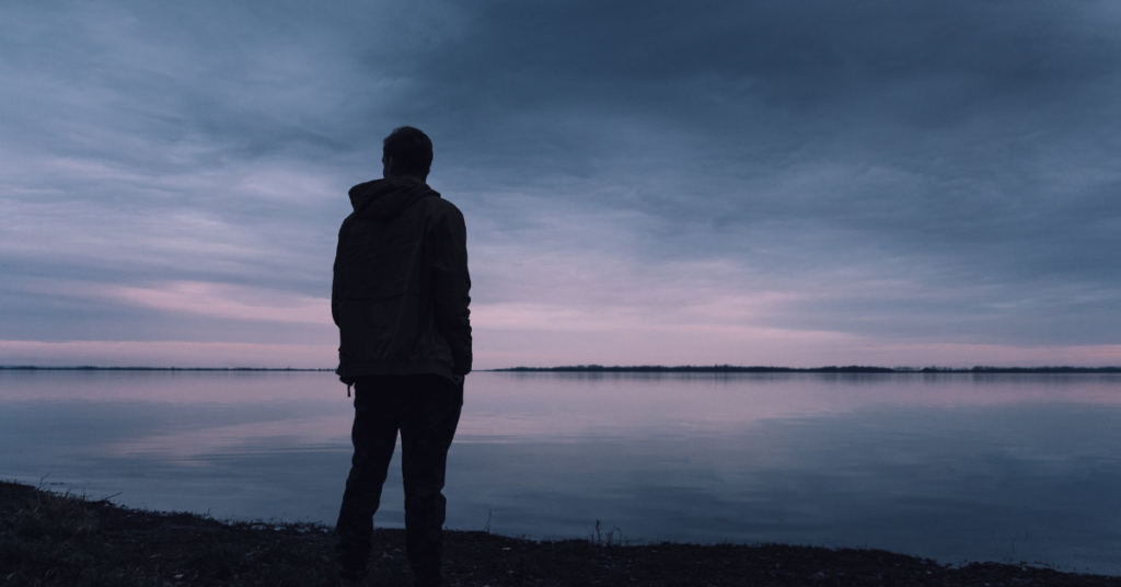 A person stands alone against a shore on a gray, overcast day.